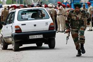 An army soldier takes runs during a fight in the town of Dinanagar, in Punjab.