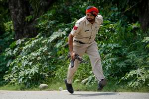 A policeman takes position during a fight in the town of Dinanagar, in Punjab.