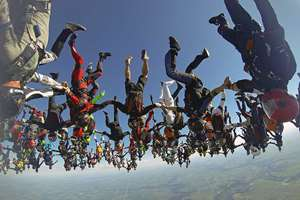 In this photo provided by Mickey Nuttall, members of an international team of skydivers join hands, flying head-down to build their world record skydiving formation, over Ottawa, Ill. It took the team 13 attempts to to build the formation, resembling a giant flower, to beat the 2012 mark set by 138 skydivers.