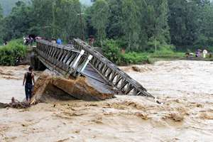 People look at the bridge which is washed away by the flood water in Thoubal District in Manipur.