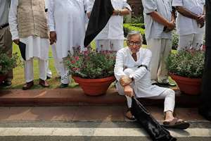 Congress party lawmaker Mani Shankar Aiyar sits with a black flag as he participates in a protest with other Congress lawmakers in the parliament premises, in New Delhi.