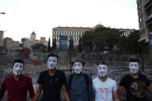 Lebanese activists wear masks as they pose for a photo in front of the government building, during a protest against the trash crisis and government corruption, in downtown Beirut, Lebanon.