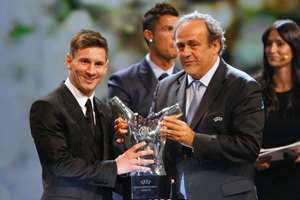 UEFA President Michel Platini, right, gives the trophy for best  player of the year to Barcelona's Lionel Messi of Argentina, during the UEFA Champions League draw at the Grimaldi Forum, in Monaco.