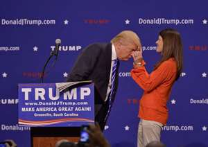 Republican presidential candidate Donald Trump has a supporter, Mary Margaret Bannister, check to see if his hair is real during his speech to supporters during a rally at the TD Convention Center in Greenville, USA.