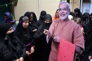 "Muslim women tie rakhis on the wrists of a cut-out of Prime Minister Narendra Modi as they celebrate ""Raksha Bandhan"" festival in Ahmedabad."