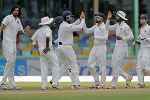 India's cricket team members celebrate the dismissal of Sri Lanka's Upul Tharanga off the bowling of Ishant Sharma on the third day of their third test cricket match in Colombo, Sri Lanka.