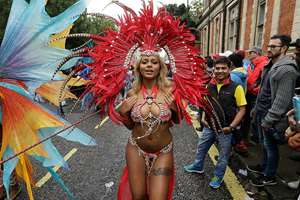 A costumed reveller performs in the Notting Hill Carnival in London.