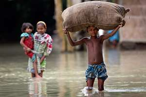 A child carries a sack through the floodwaters at Kholabuya village, 65 kilometers from Guwahati.