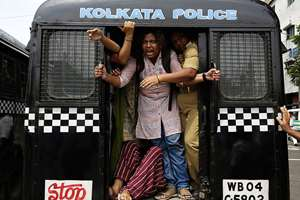 An activist of Socialist Unity Center of India shouts slogans as she is detained by the police in a van during a daylong nationwide strike called by the trade unions in Kolkata.