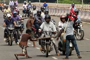 Activists of a trade union group stop motorcyclists to keep vehicles off the road during a daylong nationwide strike in the eastern Indian city Bhubaneswar.