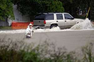 Floodwaters rise as a vehicle and a man navigate flooded streets in Florence, South Carolina. The rainstorm drenching the East Coast brought more misery Sunday to South Carolina, cutting power to thousands, forcing hundreds of water rescues and closing scores of roads because of floodwaters.