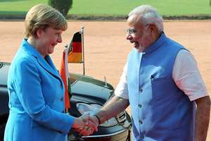Prime Minister Narendra Modi welcomes German Chancellor Angela Merkel as she arrived for the ceremonial reception at the forecourt of Rashtrapati Bhawan, in New Delhi.