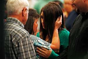 Lacey Scroggins, center right, is comforted during a church service at the New Beginnings Church of God, in Roseburg, Ore. Scroggins is a survivor of the shooting at Umpqua Community College.