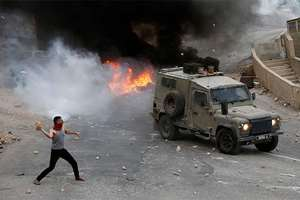 Palestinian youths throw rocks at Israeli military vehicle during a raid in the West Bank city of Nablus. Israeli Prime Minister Benjamin Netanyahu warned that he will use a strong hand to quell violent Palestinian protests and deadly attacks, signaling that the current round of violence is bound to escalate at a time when a political solution to the conflict is increasingly distant.