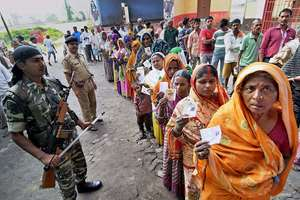 Security personnel maintaining queues of voters at a polling station during Bihar assembly elections, in Begusarai.