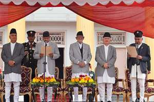 Nepal's President Ram Baran Yadav, second left, administers the oath of office to newly elected Prime Minister Khadga Prasad Oli, right, at the Presidential building in Kathmandu, Nepal.