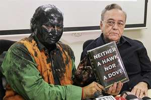Former ideologue of the BJP Sudheendra Kulkarni, with face blackened by Shiv Sena activists, and former Pakistan foreign minister Khurshid Mahmud Kasuri showing the latter's book at a press conference, in Mumbai.