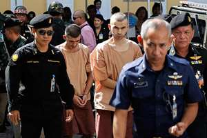 Police officers escort suspects in the Aug. 17 blast at Erawan Shrine, Bilal Mohammad, center front, and Mieraili Yusufu, rear center, as they arrive at a military court in Bangkok, Thailand. The military court has indicted two men police say carried out the deadly August bombing at the shrine that left 20 people dead and more than 120 injured.