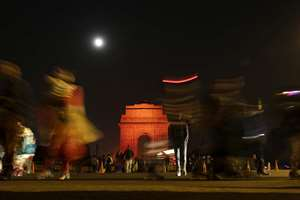 Visitors walk on a road in front of an illuminated India Gate war memorial in New Delhi. The landmark monument was illuminated in orange in an effort to raise awareness on ending violence against women.
