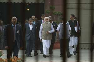 Prime Minster Narendra Modi, center, accompanied by other ministers walk to inaugurate an exhibition on the Indian Constitution, on the opening day of the winter session of the Indian parliament house, in New Delhi.