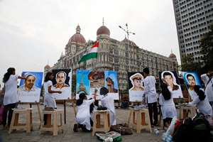 Art school students paint portraits of policemen martyrs of the Nov. 26, 2008 Mumbai terror attacks, outside the Taj Mahal Hotel, one of the sites of the attack, in Mumbai