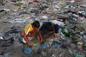 Boys search for crabs on the shores of the Arabian Sea, littered with plastic bags, in Mumbai.