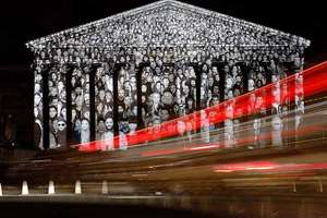 Cars pass by the national assembly in Paris, where a projection of French artist JR is displayed as part of the 2015 Paris Climate Conference. More than 140 world leaders are gathering in Paris for high-stakes climate talks and activists are holding marches and protests around the world to urge them to reach a strong agreement to slow global warming.