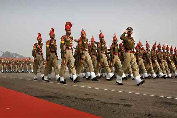 Border Security Force soldiers salute as the march past during golden jubilee celebrations of their raising day, in New Delhi.