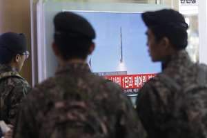 South Korean army soldiers watch a TV news programme with a file footage about North Korea's rocket launch at Seoul Railway Station in Seoul, South Korea. North Korea defied international warnings and launched a long-range rocket that the United Nations and others call a cover for a banned test of technology for a missile that could strike the U.S. mainland.