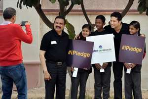 Cricket legend Sachin Tendulkar with Founder Chairman and Managing Director, Aster DM Healthcare, Azad Moopen poses with children at the launch of Aster SafeRoads campaign in New Delhi.