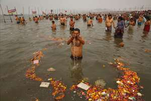 A devotee offers prayers after taking holy dip at the Sangam, the confluence of the Ganges and Yamuna rivers, on 'Mauni Amavasya' or new moon day, the third and the most auspicious date of bathing during the annual month long Hindu religious fair Magh Mela in Allahabad, Uttar Pradesh.